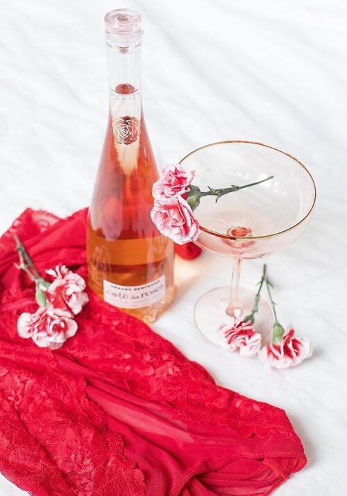 Wine, roses, and wine glass on bed.